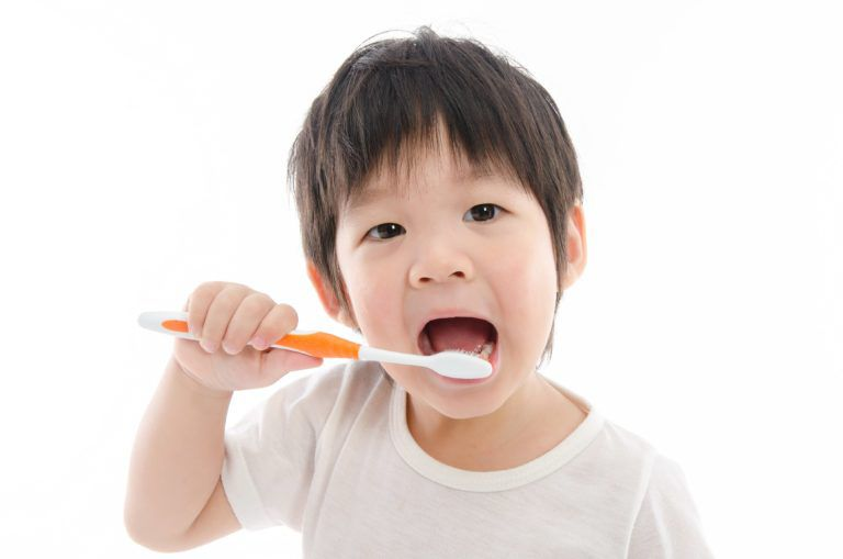 Young toddler opening his mouth and sticking in a large, orange toothbrush while slightly smiling a silly grin