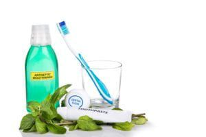 Mouthwash, toothbrush, toothpaste, and floss on a white background surrounded by mint leaves