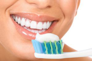 woman smiling with toothbrush and toothpaste by her mouth