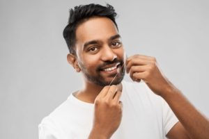 man flossing his teeth against a grey background