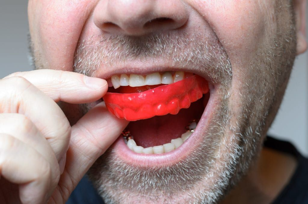 Close up of a man placing a red mouth guard