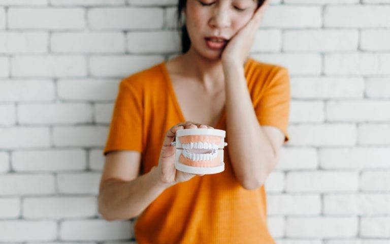Woman Displaying Model With Tooth Pain